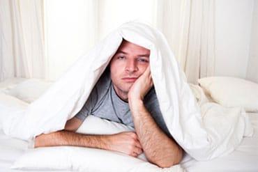 Homme avec chandaille gris fatigué dans lit insomnie trouble du sommeil